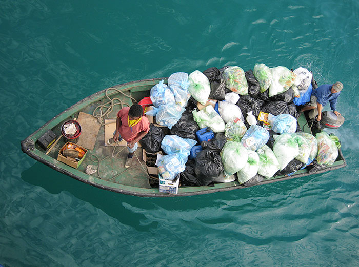 Tourist impact: A dinghy picks up trash and recycling from yachts moored in Academy Bay in Puerto Ayora, Santa Cruz Island. ©Joshua Brockman 2007. All Rights Reserved.