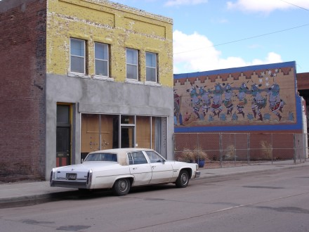 A white Cadillac sits idle, outside a yellow brick building, facing a mural of Indian dancers in Winslow, Ariz. ©Joshua Brockman 2005. All Rights Reserved.